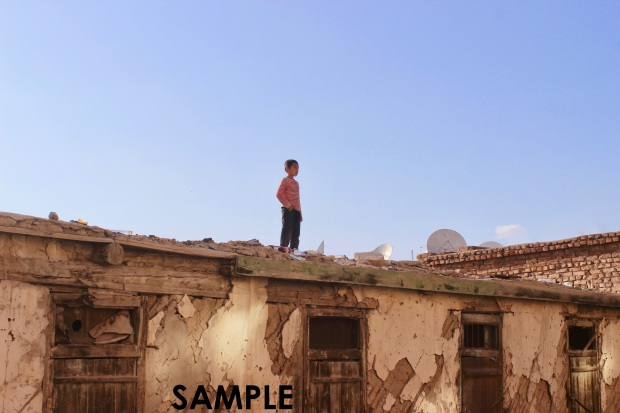 A lone child playing on a dilapidated rooftop in a small Mongolian village.